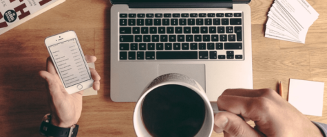 Man drinks coffee while working on Macbook and holding phone   Vox ICT