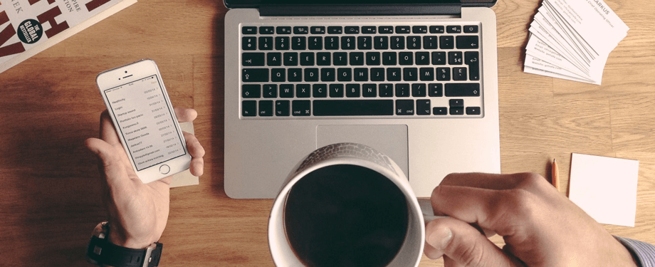 Man drinks coffee while working on Macbook and holding phone | Vox ICT
