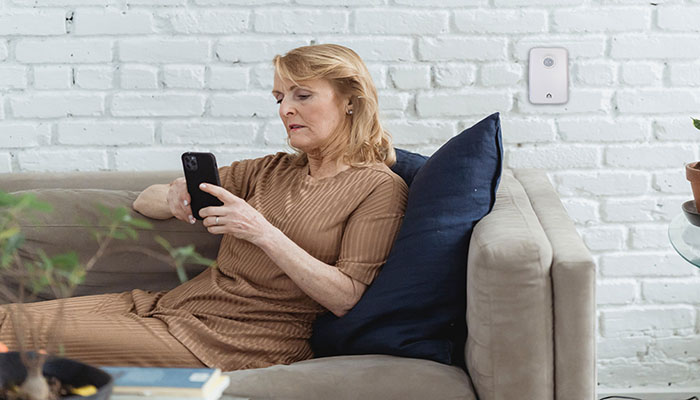 Older woman at home on the couch with Vox I.C.E on the wall behind | Vox In Case of Emergency | Monitoring Technology | Vox IoT| image